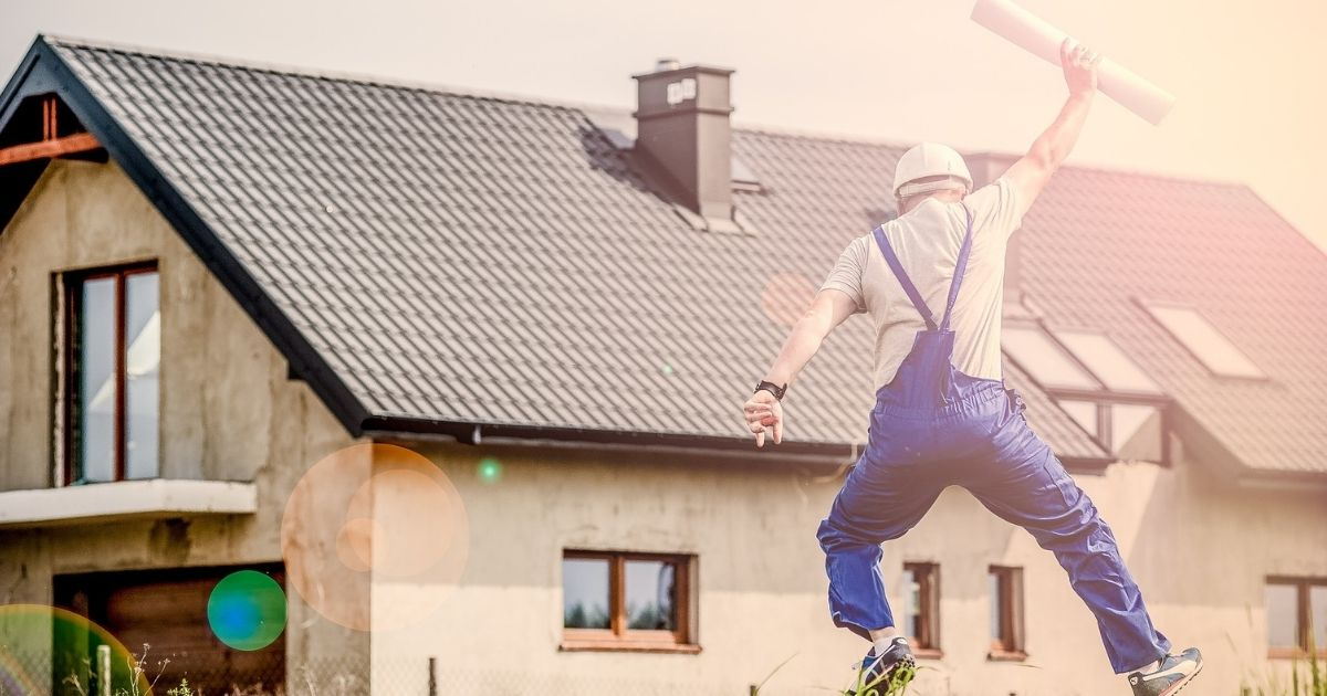home builder tradesperson jumping for joy outside house with plans in hand